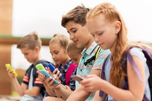 elementary school students with smartphones - kind vor der pubertät stock-fotos und bilder