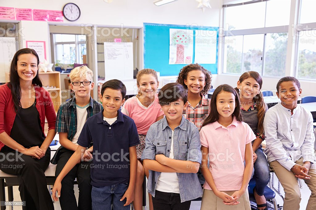 Elementary school teacher and her pupils in classroom stock photo