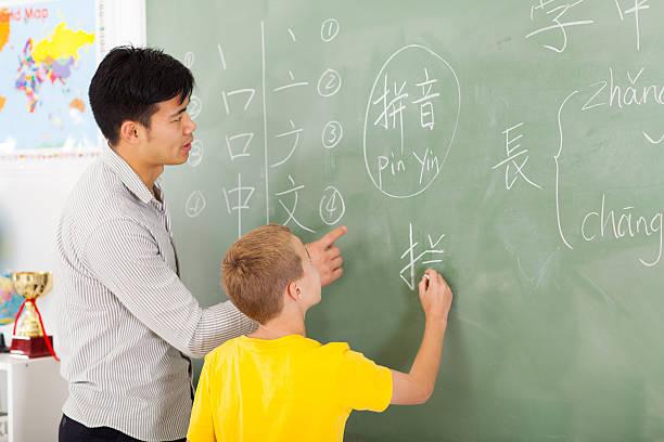 professor de escola primária ajudando a jovem rapaz de escrita chinesa - aula de idioma - fotografias e filmes do acervo
