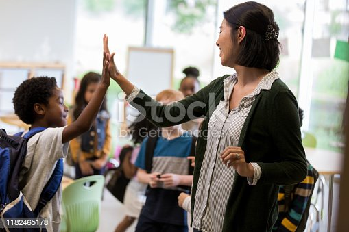 Cheerful young Hispanic elementary school teacher gives a high five to a student before class.