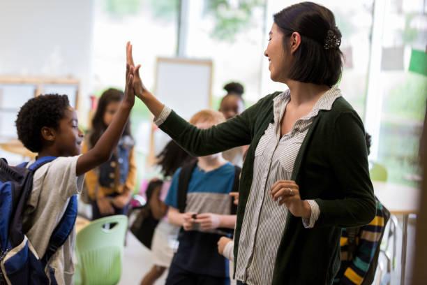 Elementary school teacher high fives student stock photo
