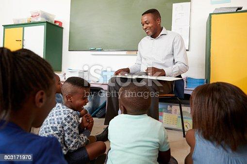istock Elementary school teacher reading to kids sitting on floor 803171970