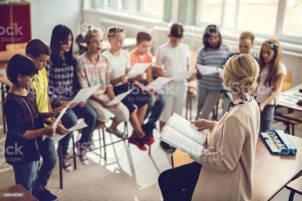 Elementary school teacher singing with children in the classroom. stock photo