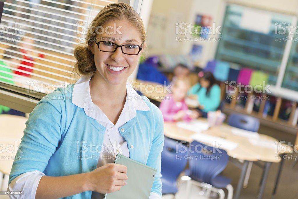 Elementary school teacher standing in doorway while students take test stock photo