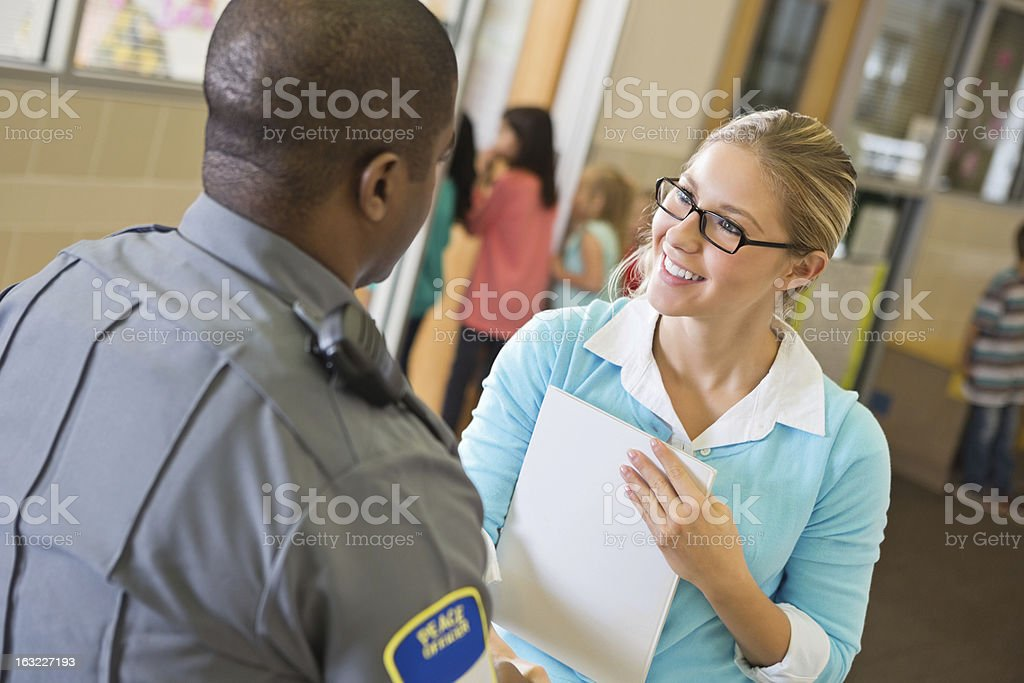 Elementary school teacher talking with police officer in hallway royalty-free stock photo