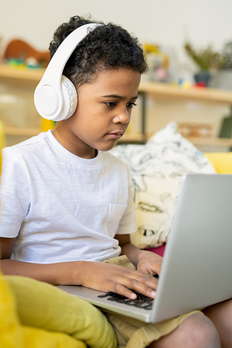 Serious elementary schoolboy of African ethnicity with headphones typing on laptop while listening to educational online course at home