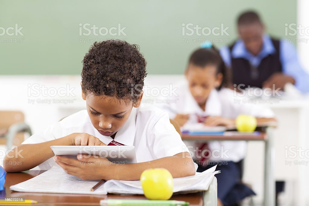 elementary schoolboy using a tablet computer stock photo