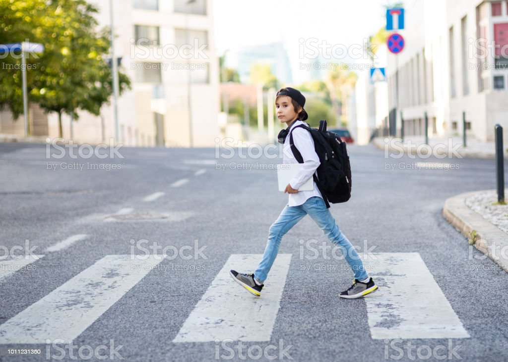 Elementary schoolboy with backpack crossing the road stock photo