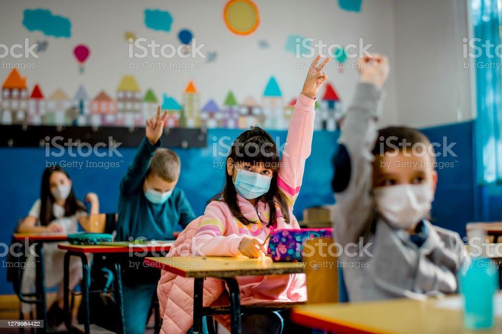 Grundschüler tragen im Klassenzimmer eine schützende Gesichtsmaske. Bildung während der Epidemie. - Lizenzfrei Schulgebäude Stock-Foto