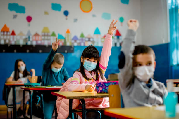 Elementary schoolchildren wearing a protective face masks  in the classroom. Education during epidemic. Elementary schoolchildren wearing a protective face masks  in the classroom. Education during epidemic. education stock pictures, royalty-free photos & images