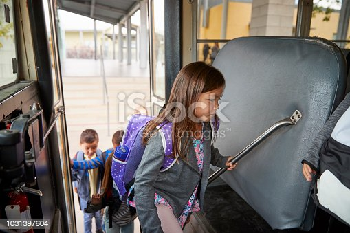 1031397608 istock photo Elementary schoolgirl getting on the school bus to go home 1031397604