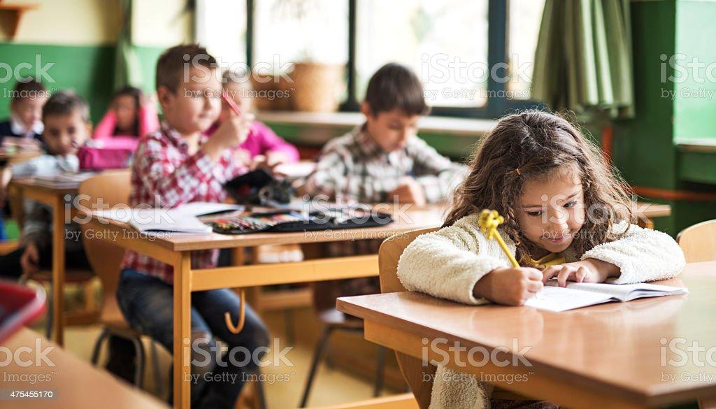 Niña en edad escolar primaria en clase escribiendo en el aula. - foto de stock