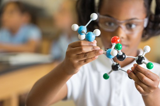 Elementary science student using plastic atom model educational toy