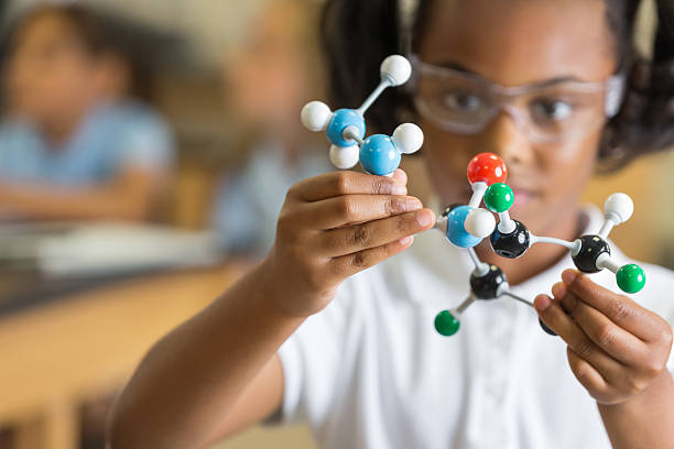 Elementary science student using plastic atom model educational toy stock photo