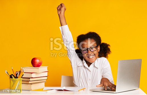 Black Elementary Student Girl Raising Hand Sitting At Laptop Doing Homework Over Yellow Background. Studio Shot