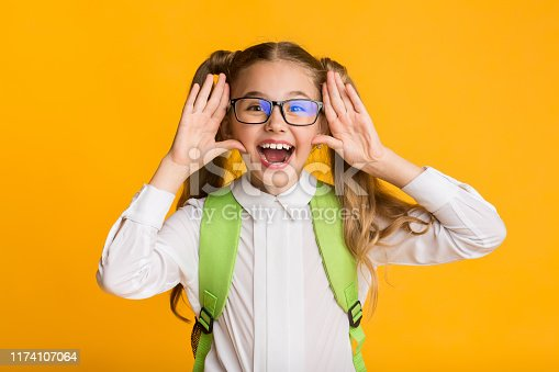 1176772377 istock photo Elementary Student Girl Shouting Holding Hands Near Mouth, Yellow Background 1174107064