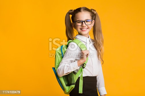 1176772377 istock photo Elementary Student Girl Smiling Looking At Camera In Studio 1174100479