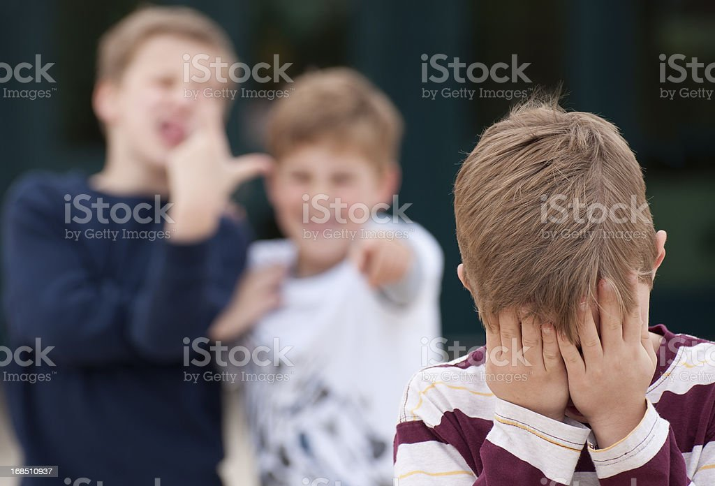 Elementary Student Hides His Face While Being Bullied stock photo