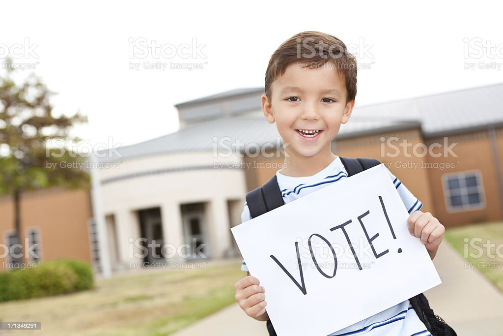 Elementary student holding a Vote sign in front of school stock photo