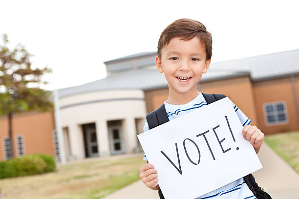 elementary student holding a vote sign in front of school - vote sign stock photos and pictures