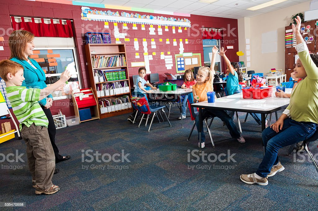 Elementary student in front of his class stock photo