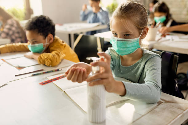 Elementary student wearing protective face mask and disinfecting her hands in the classroom. Schoolgirl with face mask using hands sanitizer while sitting at a desk in the classroom. school building stock pictures, royalty-free photos & images