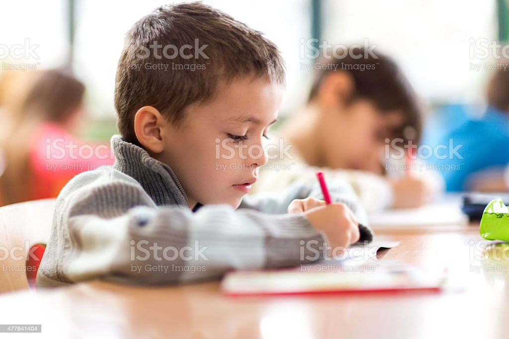 Elementary student writing in a notebook during a class. stock photo