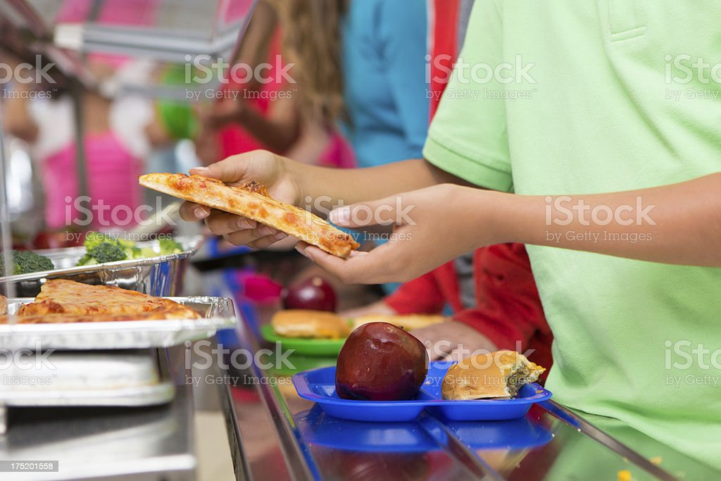 Elementary students choosing healthy/unhealthy food in school cafeteria line royalty-free stock photo