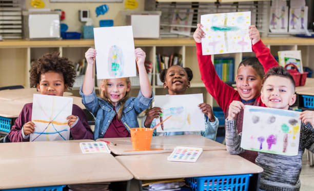 Elementary students in art class, holding up artwork stock photo