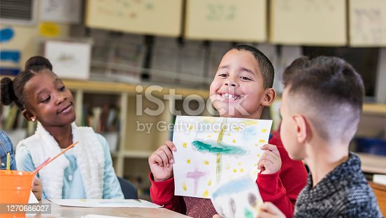 Three elementary school students, 7 and 8 years old, in art class. They are sitting together at a table. An Hispanic boy is proudly holding up the picture he painted, smiling as he shows the viewer.