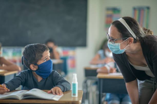 Elementary students in the classroom wearing masks stock photo