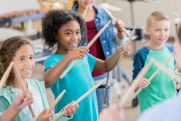 Elementary students learn to play percussion instruments stock photo