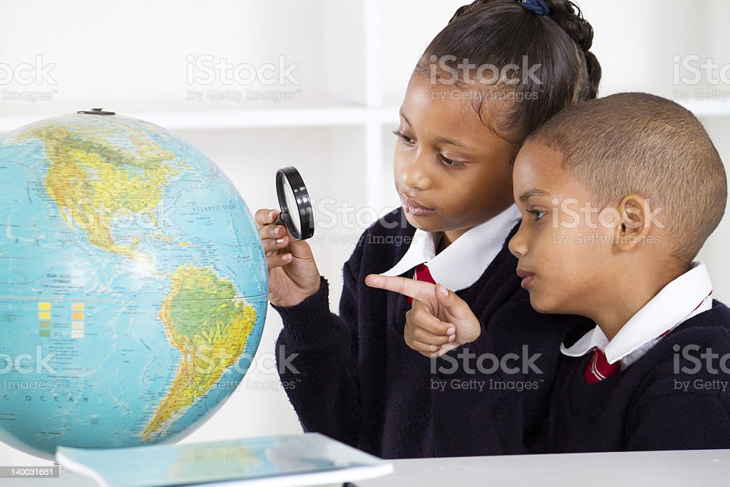 elementary students looking at globe royalty-free stock photo