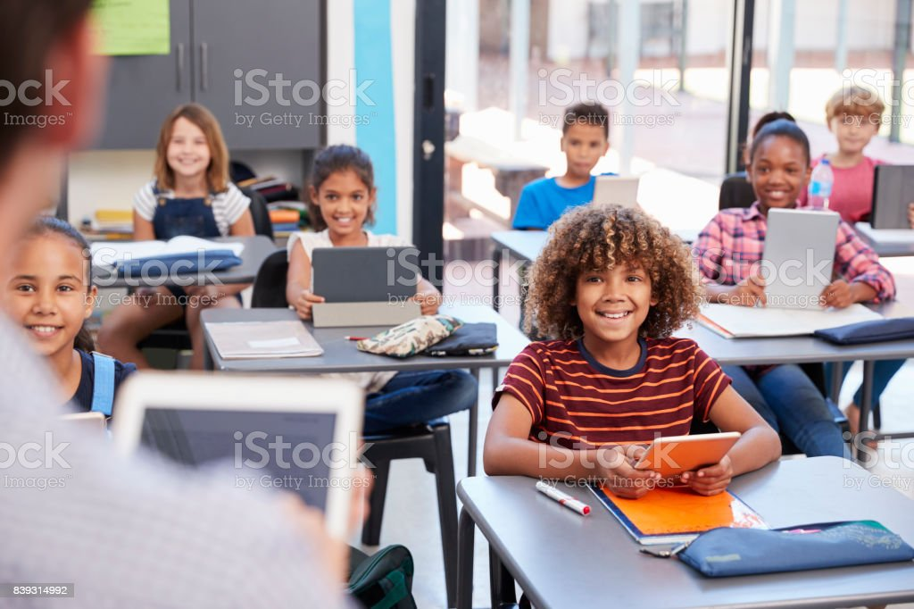 Elementary students looking at teacher, over shoulder view royalty-free stock photo