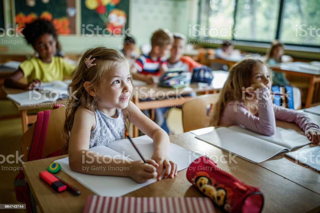 Elementary students paying attention during a class in the classroom. stock photo