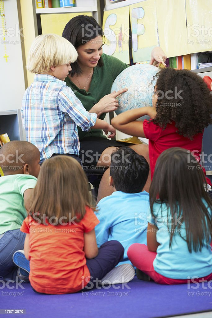 Elementary students studying geography with globe stock photo