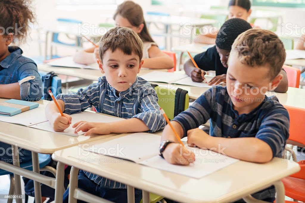 Elementary students taking a test in classroom. – Foto