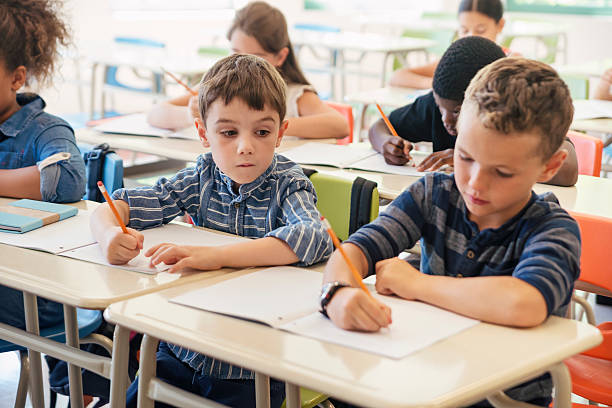 Elementary students taking a test in classroom. stock photo