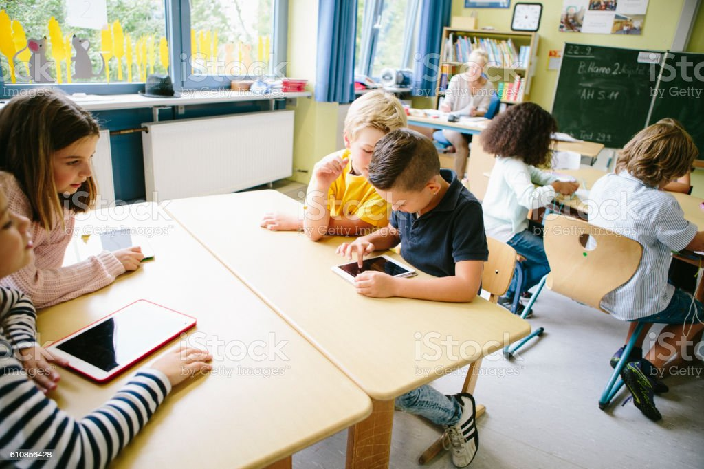 Elementary Students use digital tablets in the classroom stock photo
