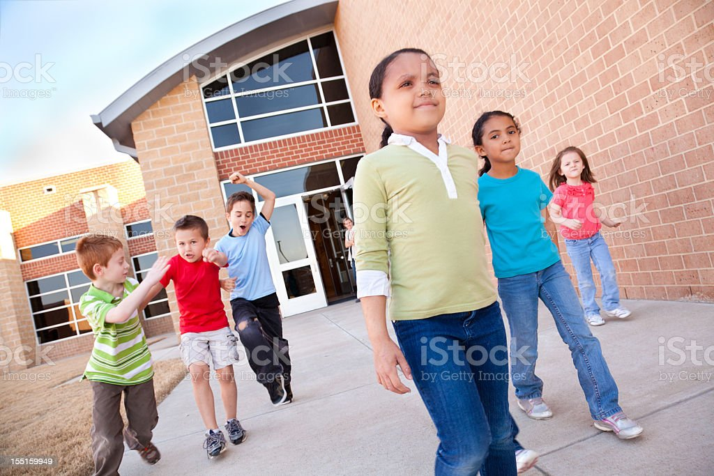 Elementary Students Walking Out of School Building Together royalty-free stock photo
