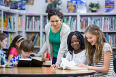 istock Elementary students working with teacher in library 512994084