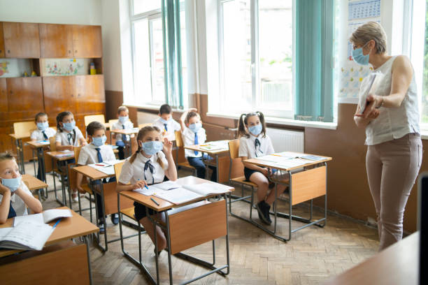 COVID-19. Elementary teacher doing classes during Coronavirus pandemic stock photo