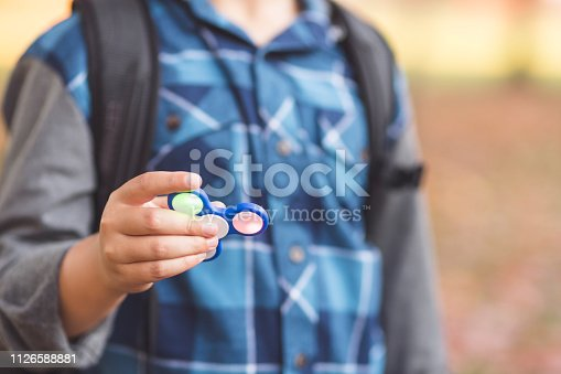 istock Elementary-age boy holds up a fidget spinner 1126588881