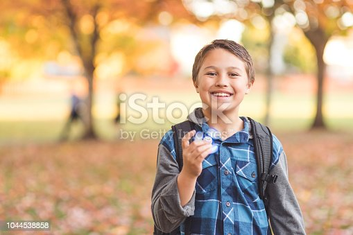 istock Elementary-age boy walking to school and holding a fidget spinner 1044538858