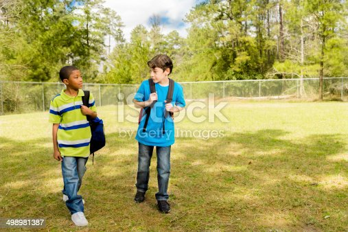 African descent and Latin descent boys walk to school across the campus carrying backpacks.  Sunny spring day.  Friendship.