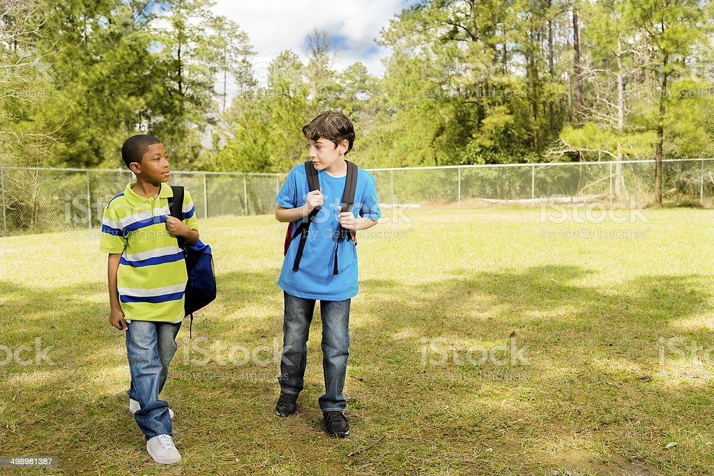 Elementary-age boys walk to school. Campus or park. Friends. stock photo