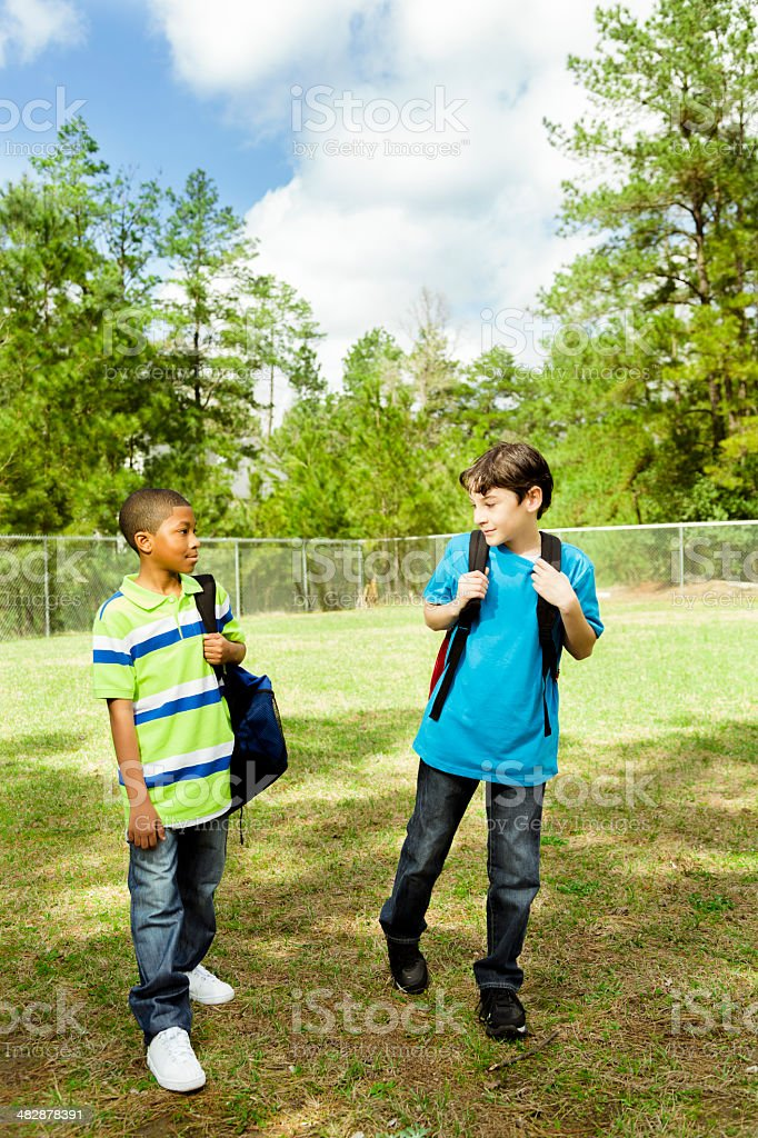Elementary-age male friends walk to school. Campus or park. stock photo