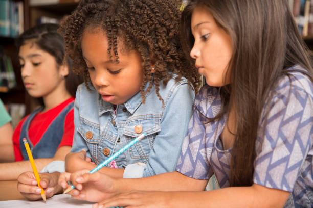 小学校時代の学校の女の子は、宿題の共同作業します。 - 作文の授業 ストックフォトと画像