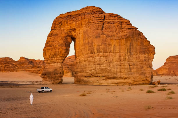 Elephant Rock near Al Ula Saudi Arabia Man walks toward Elephant Rock near Al Ula, Medina Region, Saudi Arabia at sunset. saudi arabia stock pictures, royalty-free photos & images