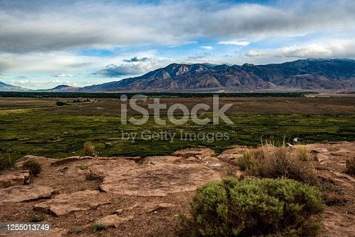 Elevated cliff view of lower green Owens River valley and distant Eastern Sierra Nevada mountain range under cloudy sky.